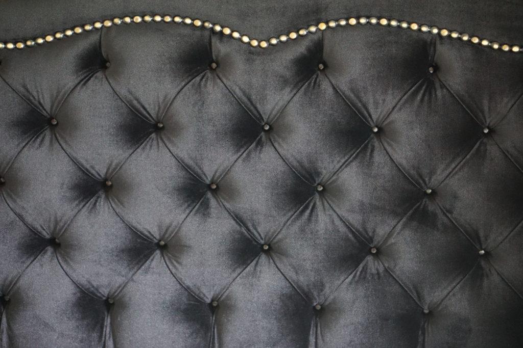 Black velvet bedhead with gold stud detail